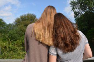 2 Freundinnen, die die Köpfe zusammen stecken; Bild zu: Vertraute Gespräche